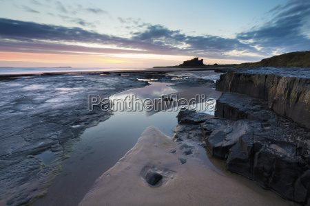 view towards bamburgh castle at sunrise