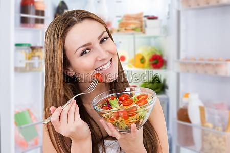 junge frau die salat isst