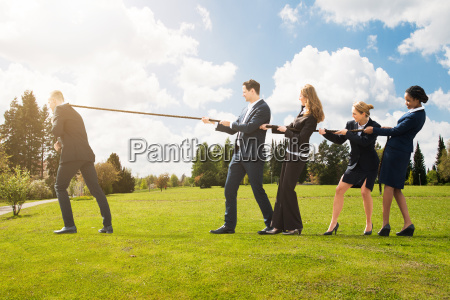 business people pulling a rope in