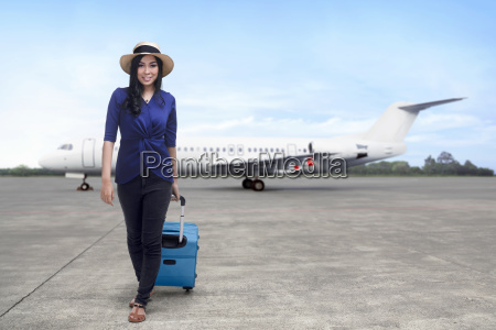 young asian woman pulling blue suitcase