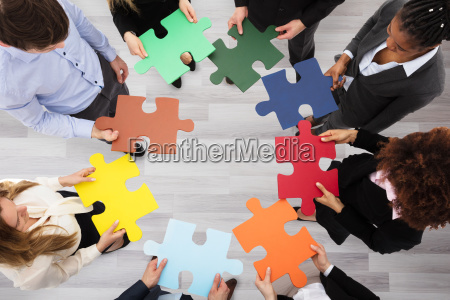 business people holding colorful jigsaw puzzles
