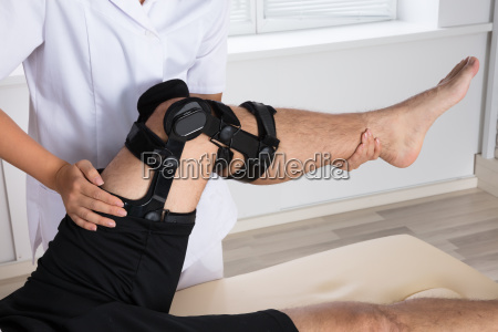 physiotherapist fixing knee braces on mans