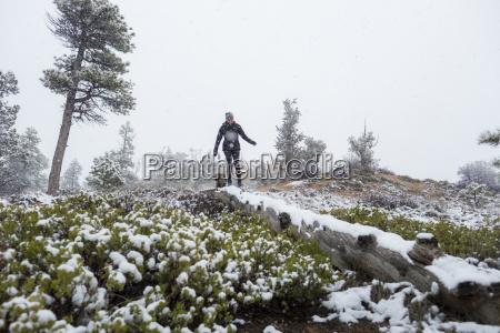 woman walking on fallen tree in