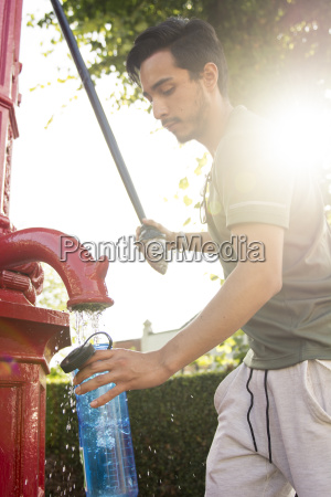 young man pouring water into bottle