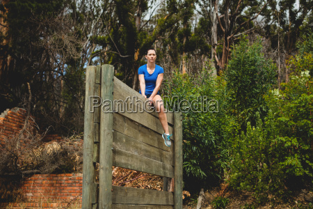 fit woman sitting over wooden wall