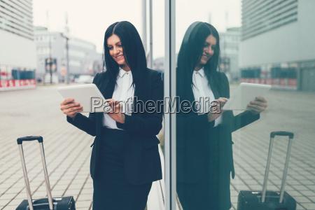 junge geschaeftsfrau mit tablet und koffer