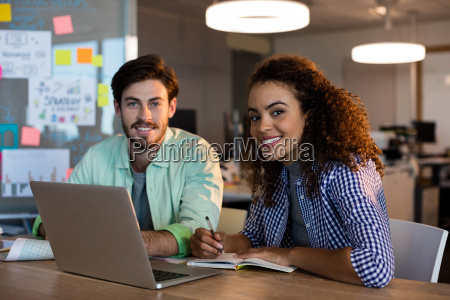 smiling creative business people with laptop