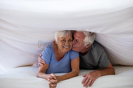 senior man kissing woman under blanket