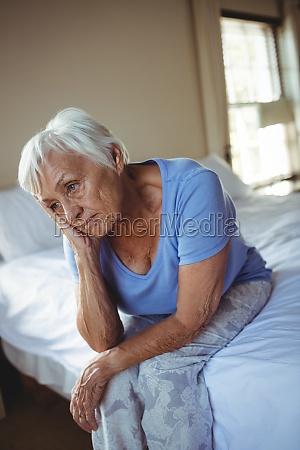 worried senior woman sitting on bed