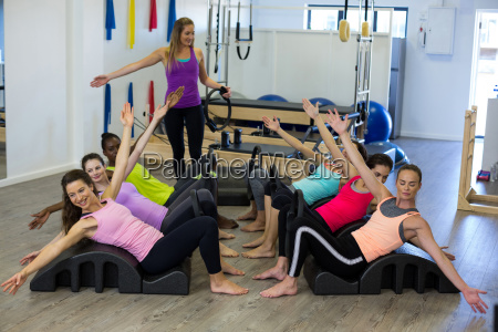 female trainer assisting group of women