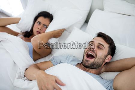 woman getting disturbed with man snoring