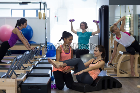 female trainer assisting woman with stretching