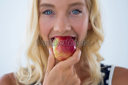 portrait of beautiful woman eating red