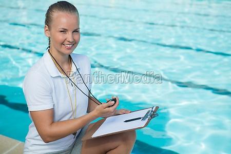 smiling swim coach holding zwischenablage und