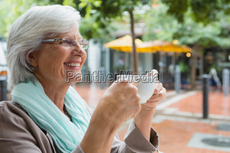 senior woman holding a coffee cup