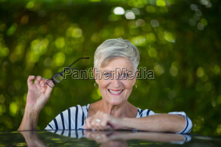 senior woman holding eyeglasses by car