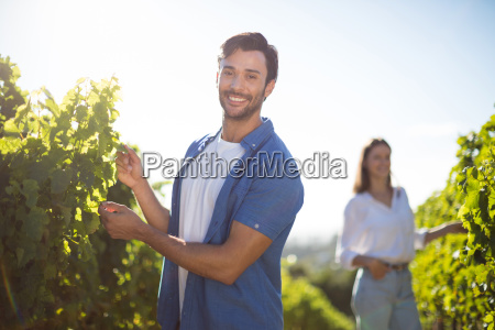happy couple standing by plants growing