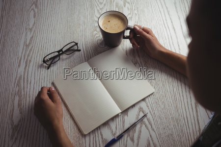businesswoman holding coffee cup on desk