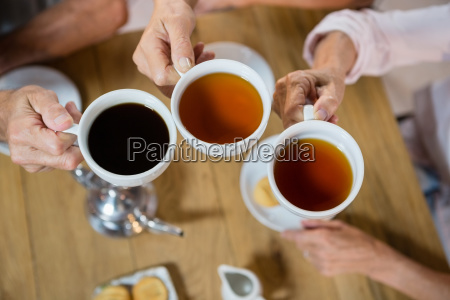 group of senior friends toasting coffee