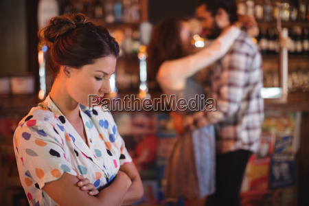 upset woman ignoring affectionate couple