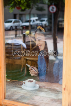 smiling woman holding mobile phone while