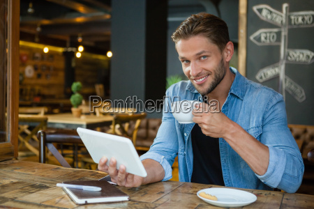 portrait of smiling man using digital