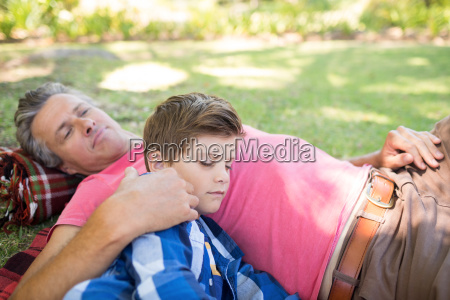 father and son sleeping on picnic