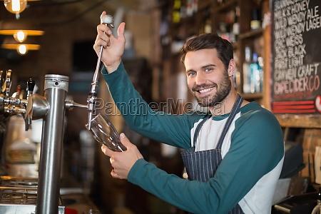portraet von barkeeper giessen bier aus