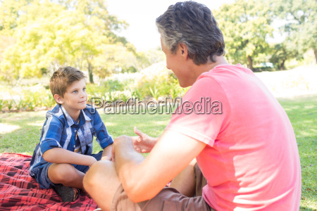 father talking to son at picnic