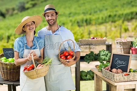 retrato de pareja sonriente sosteniendo verduras