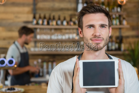 portrait of smiling waiter showing digital