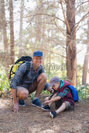 happy father kneeling by boy tying