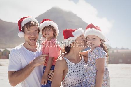 cheerful family wearing santa hat at