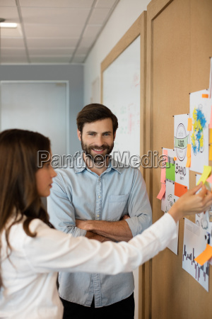 smiling businessman with female colleague analyzing