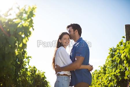 smiling woman hugging boyfriend amidst plants