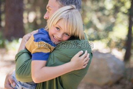 smiling boy embracing father in forest