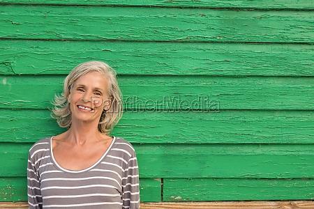 smiling senior woman standing against green