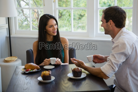 smiling young couple sitting at cafe
