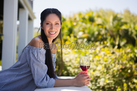 confident woman holding red wine glass