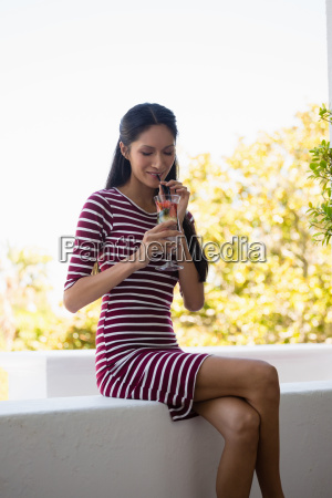 woman drinking cocktail while sitting on