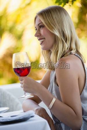 attractive woman holding red wine glass