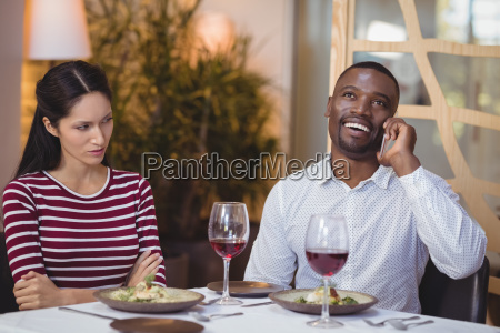 man ignoring bored woman while talking