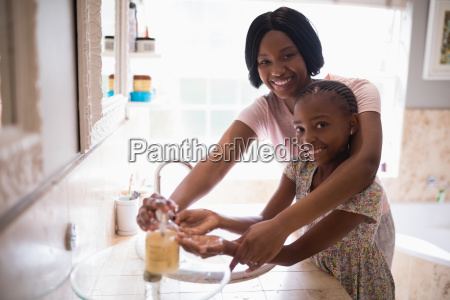 smiling mother assisting daughter while washing