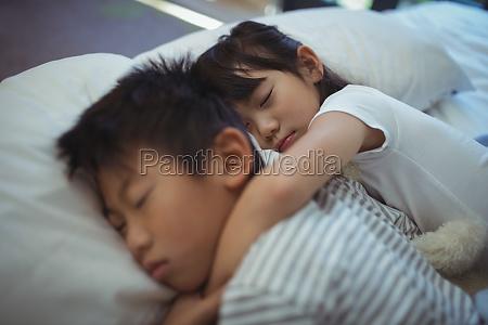 geschwister schlafen im bett