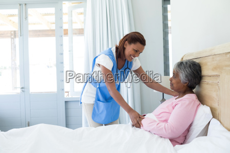 female doctor comforting senior woman on