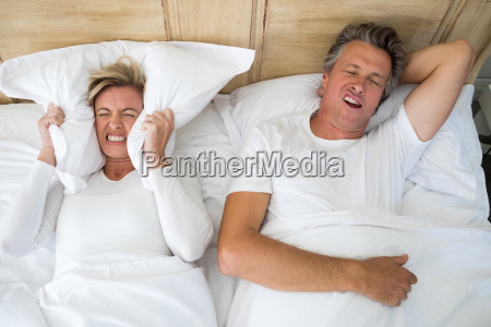 annoyed woman covering ears with pillow