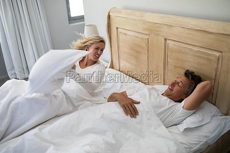 woman getting irritated while man snoring