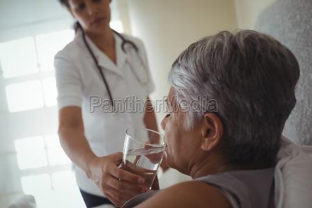 female doctor giving sick senior woman