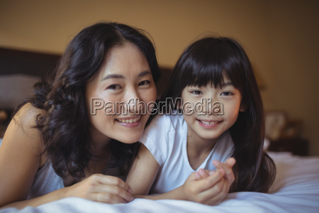 mother and daughter relaxing on bed