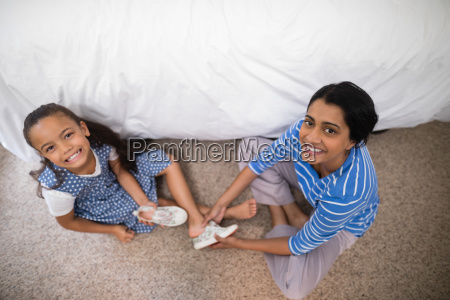 portrait of mother helping daughter to